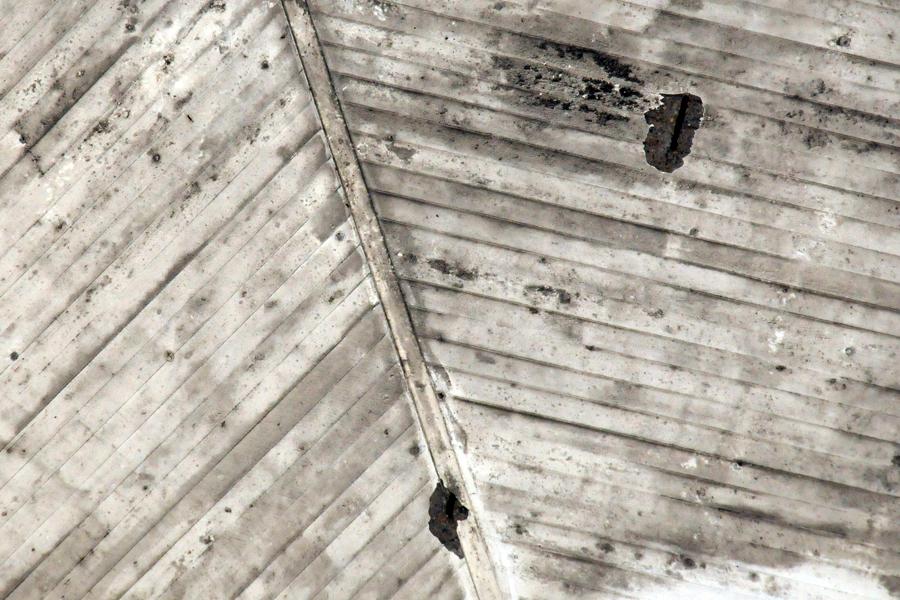 Från marken syns hur betongen släppt från vilplanet, 45 meter upp. Armeringsjärnet syns tydligt i sprickorna.