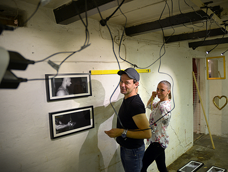 Urinvånarnas gästutställare Jonas Westring och Josefine A Olsson arbetar in i det sista med att få bilderna snyggt upphängda på det svårspikade väggarna.