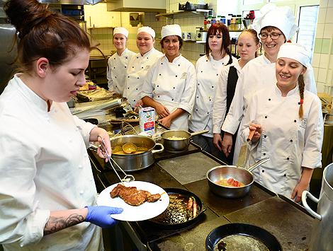 Pia Sönnichsen, tvåa från höger, instruerar hur en schnitzel ska läggas upp. Till en elevs förvåning skulle köttbiten ha en ansjovisfilé på.