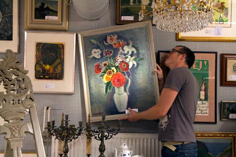Joakim Karlsson hänger en stilleben av Agda Holst. En tavla som han hoppas ska locka konstintresserade till tisdagens onlineauktion.