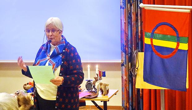 Majvor Massa Eriksson bredvid den samiska flaggan