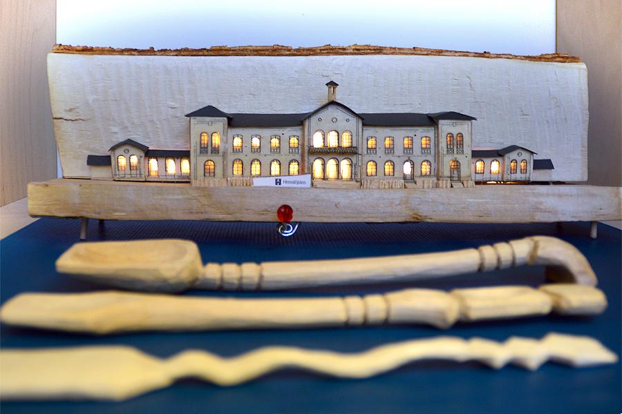 Hemslöjdens hus i Landskrona tillsammans med tre slevar slöjdade ur ett vedträ.