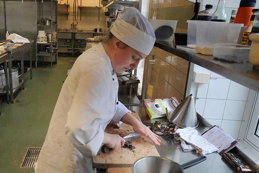 Alexandra Hedin hackar choklad som sedan ska smältas ner och till slut bli en del av efterrätten.