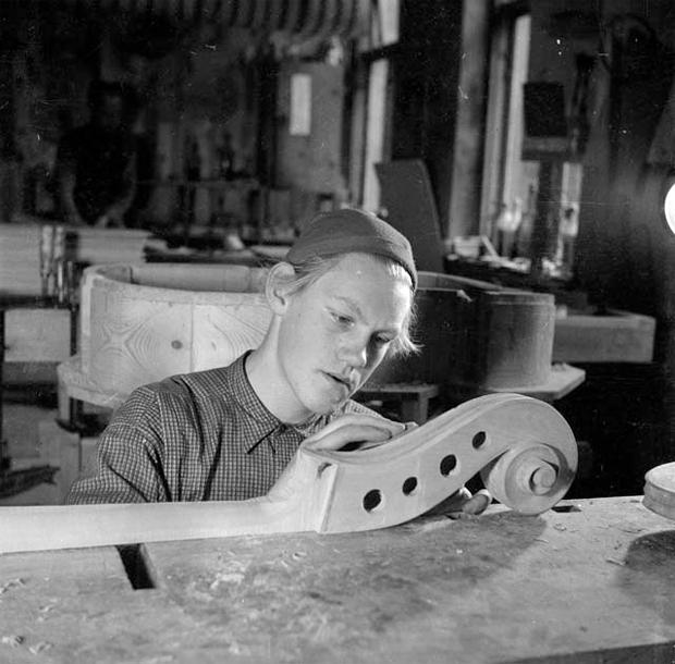 Sigvard Mattsson putsar snäckan på en basfiol i verkstaden. Arbetade där 1943-1951. S.M. byggde kontrabas = största artikeln. C:a 500 st tillverkades. En del gitarrer. Firman tillverkade först trummor. Firman nedlagd 1951 p.g. av konkurrens av importen Foto: GeWe (1945). /Minnesbanken Landskrona museum