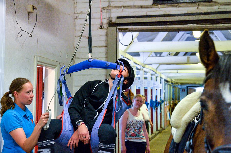 Emelie Warmenius använder lyften för att hjälpa Johanna Lindahl upp i sadeln. Foto: Ulf Bjarke – Foto261.se
