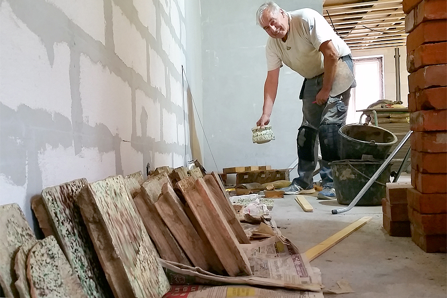 Kakelplattorna står uppradade i den ordning de ska muras upp.