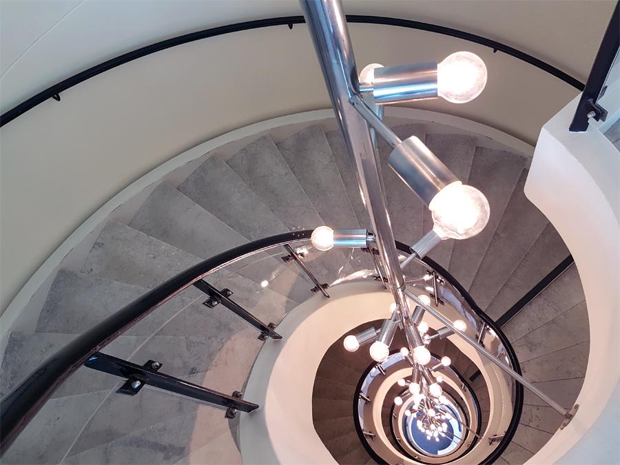 Den specialtillverkade armaturen som löper längs hela trapphuset känns än idag väldigt modern.