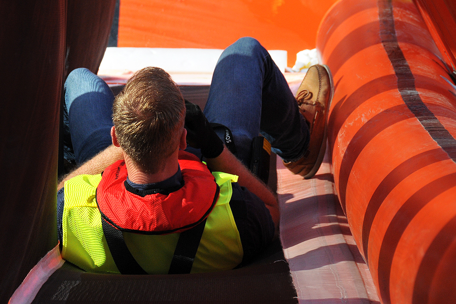 Linus Olsson tar sig ner till livflotten helt enligt manualen. Med armarna i  kors över bröstet samtidigt som han bromsar nerfarten med fötterna i sidan av sliden.
