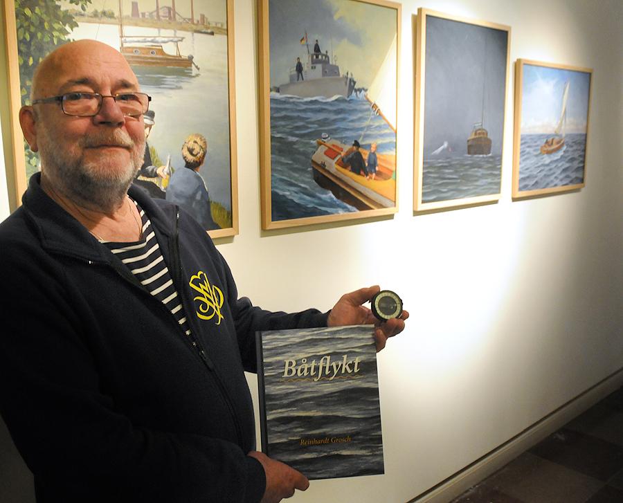 Reinhardt Grosch med luftkompassen i handen och sin nyligen utgivna bok, Båtflykt, berättar han historien om sin flykt till Sverige från DDR.